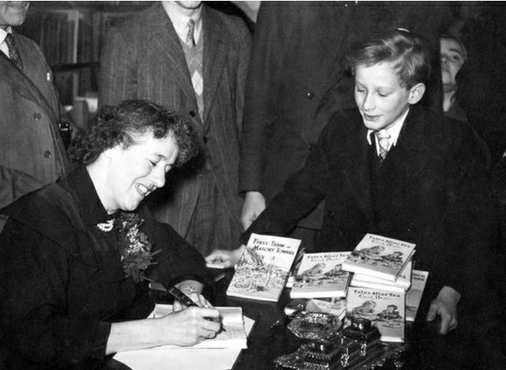 "Enid Blyton in Hatchards, Piccadilly, London, where she gave a talk 'for children only', adults not being admitted. Afterwards she autographed copies of her books for her young audience. She obliges ""Oliver Twist"" (John Howard Davies who played the film part in 1948 for David Lean) with a signed copy of one of her books. JHD would go on to produce Monty Python, Steptoe and Son, Fawlty Towers and the Good Life."