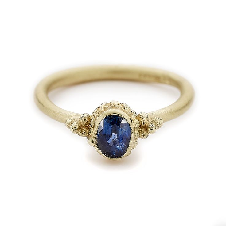 Unique oval sapphire solitaire engagement ring in yellow gold. Handmade in Ruth Tomlinson's London studio, perfect for the alternative bride with vintage style.