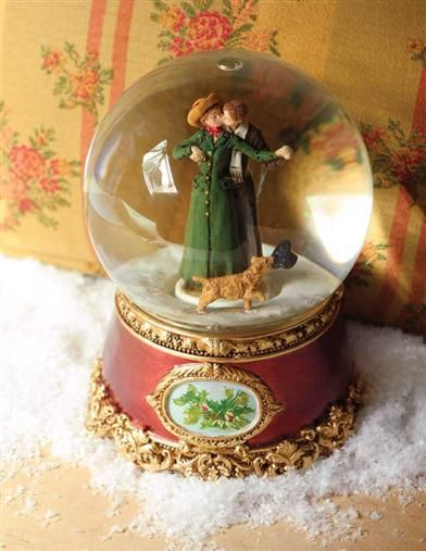 A CHRISTMAS KISS SNOWGLOBE >  A prancing pooch with a retrieved top hat encircles lovers to the beloved Greensleeves melody as opalescent snowflakes descend upon them. Wind-up mechanism. Crystal globe. Hand painted base. 7. Gift boxed.