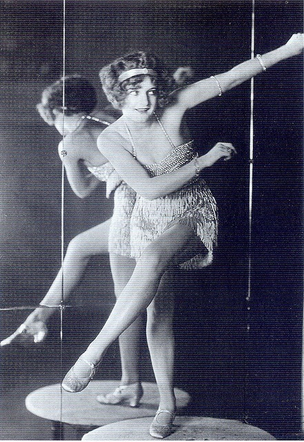 """From the book: """"World champion Charleston dancer Bee Jackson wears a beaded and fringed dance dress, popular at the time, as the fringes would shimmer and shake and draw attention to movement. This dress is shorter than the typical styles of the era. Paste jewellery known as """"slave bracelets"""" was often worn high up on the arm as well as the wrist.""""    Scanned from """"Decades of Fashion"""" by Harriet Worsley."""