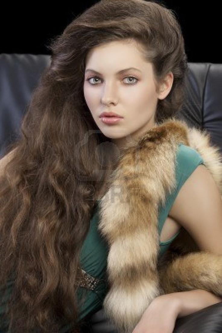 ritratto di una donna sofisticata ed elegante seduto su un divano nero con stile di capelli e indossando un abito verde e un pelo della coda guardando a porte chiuse Archivio Fotografico
