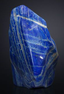 LAPIS LAZULI (The main component of lapis lazuli is lazurite (25% to 40%), a feldspathoid silicate mineral. Most  also contains calcite (white), sodalite (blue), and pyrite (metallic yellow). Some lapis lazuli contains trace amounts of the sulfur-rich löllingite variety geyerite.  Lapis lazuli usually occurs in crystalline marble as a result of contact metamorphism.)- Afghanistan