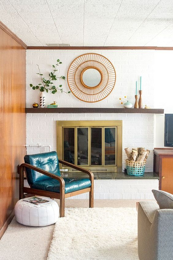 Mid Century Modern styled wooden mantel with mirror, candlesticks, and plant.
