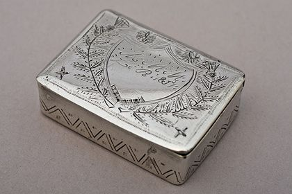 """A charming Cape silver snuffbox, retangular in form, and quite small in size. It is decorated with typically Cape engraving, generally a crude series of lines and dots. The cover is quite unusual, having a central shield cartouche (engraved """"MMM Le R 1851"""") surrounded by 2 Scottish thistles - this design is very rare on Cape silver. The surname """"Le R"""" (possibly Le Roux?) is probably French Huguenot in origin, the Scottish thistles are a mystery. The sides of the box have a zig-zag design…"""