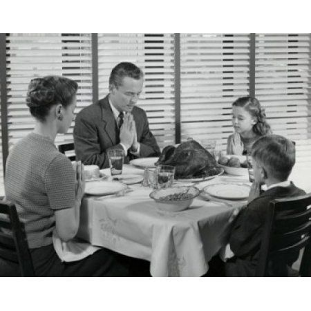 Mature couple with their two children praying at a dining table on Thanksgiving Day Canvas Art - (24 x 36)