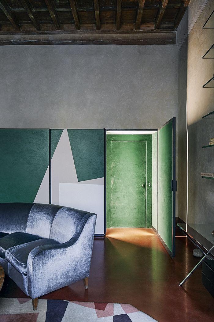 La maison de RobertoBaciocchi en Toscane Dans la Salle à manger, le long placard, peint par un ami, dissimule une porte. Le canapé vintage est recouvert de velours bleu gris et le tapis date des années 1980.