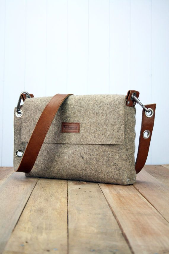 "Mens felt satchel bag which is handmade from 3 mm industrial wool felt, which is assembled using pop rivets. The strap is made from 100% vegetable tanned full-grain leather which is backed with wool felt and fastens onto the bag with carabiners.  The front flap fastens with a magnetic snap and there are internal pockets for your phone and wallet.  Dimensions:  Length 14"" / 36cm  Width 10"" / 25cm  Depth 2.5"" / 6cm  This bag, like all my items, are designed and made by myself in London, UK. I…"