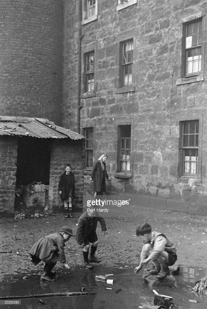 Boys play in a puddle in the slums of Gorbals Glasgow The Gorbals tenements were built quickly and...