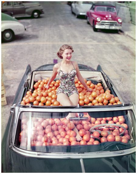 irca 1951. %22Swimsuit model in Cadillac convertible filled with oranges.%22 We don't know the where, the who or the why