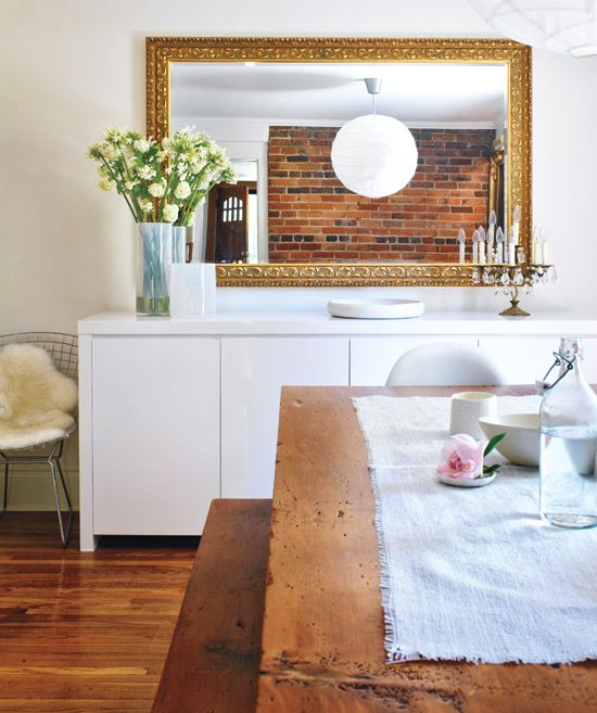 I love the juxtaposition of the antique mirror with the modern sideboard.: