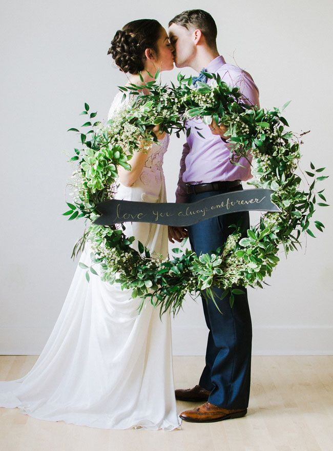 Love this foliage wreath with banner. Such a cute bride & groom!