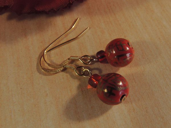 Made with burnt orange ceramic beads which have gold designs on them reminiscent of Chinese characters, I have emphasised the colour with a small red glass bead