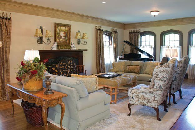 The formal living room of this 1930s home reflects its Tudor styling with the original arched windows, fireplace and mantel.