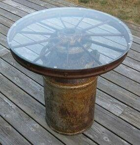 Old Milk Can amd Old Wagon Wheel With A Piece Of Glass On Top.