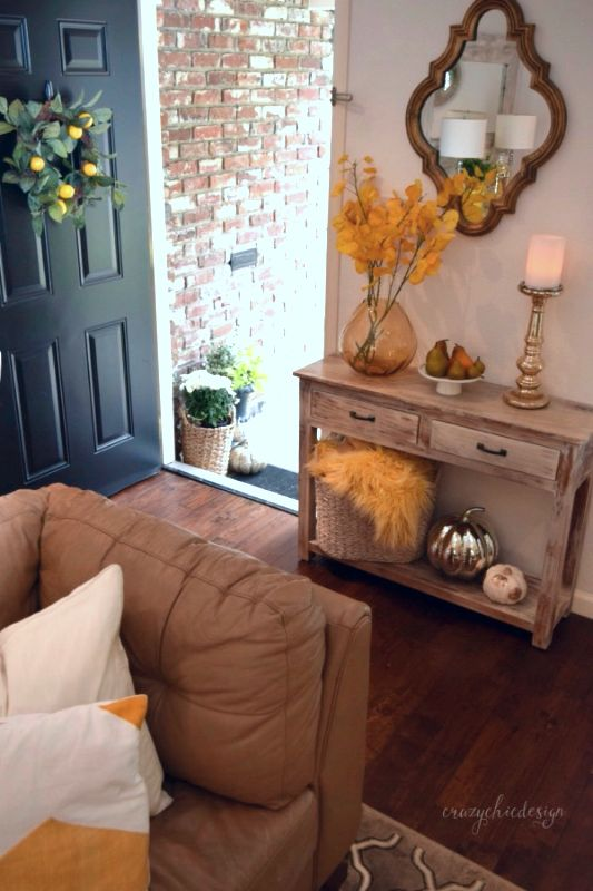 Welcome your guests with a festive Fall entry.  Use a small accent table by the door for displaying your favorite fall accessories like: pumpkins, vases, baskets, fruits and candles.  HomeGoods Sponsored Pin.