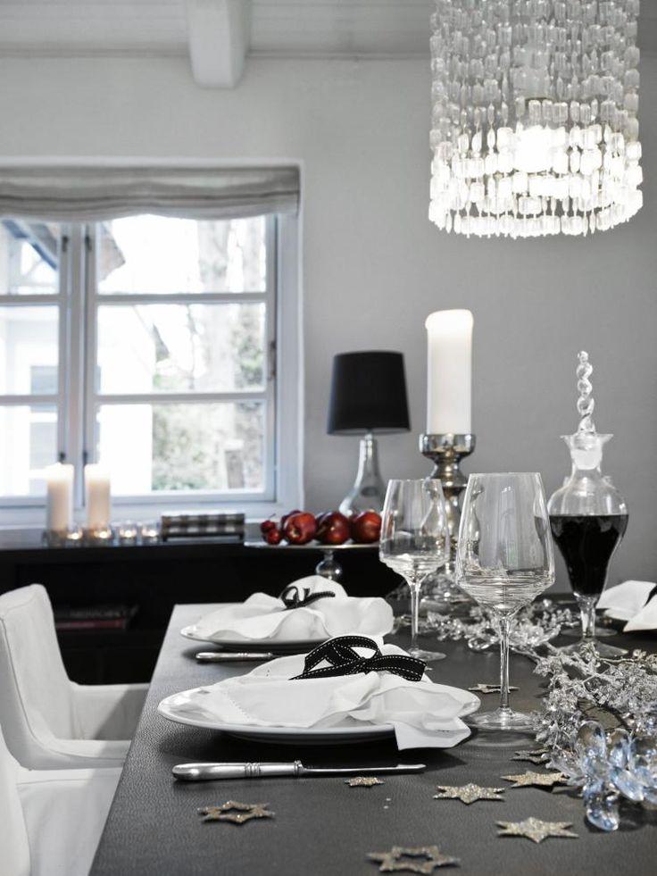 Den imponerende prismelampen slipper seg over bordet som et glitrende fossefall av julestemning. Spisestuestolene er fra Ikea og bordbukken fra Ilva. Eieren har innredet stue og spisestue med kontrastene svart og hvitt, og har tilført elementer i sølv og gull for litt julestemning.