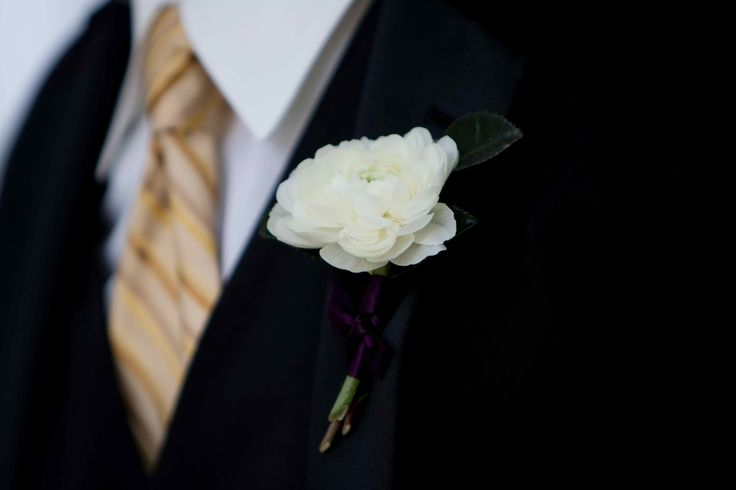 a white ranunculus boutonniere for the groomsman is a standout on the lapel of his black tuxedo.