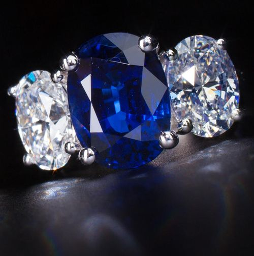 A sapphire and diamond ring; set with an oval-cut sapphire, weighing 6.60 carats, flanked by oval-cut diamonds, weighing 2.02 and 2.03 carats; mounted in eighteen karat white gold; size 6 1/4. Via Bonhams.