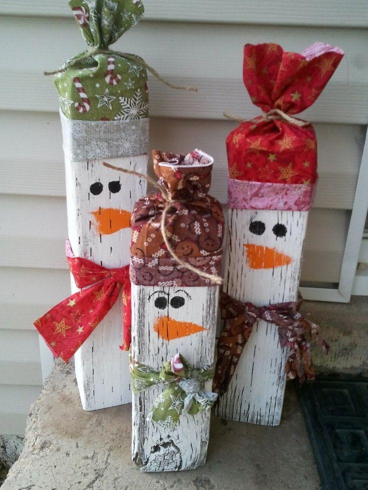 drei Schneemänner aus Holz mit selbstgenähten Mützen