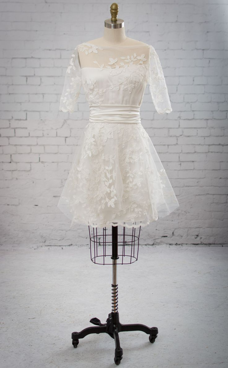 Audrey by Martin McCrea   Convertible wedding dress ensemble of a mini dress, flutter skirt, and cummerbund sash. Mini dress of appliquéd tulle with an organic bateau neckline and two layers of silk charmeuse underneath. Elbow length sleeves. Flutter skirt has layers upon layers of silk georgette fashioned in a multitude of angles. Mini dress alone (as shown) makes a lovely reception dress.