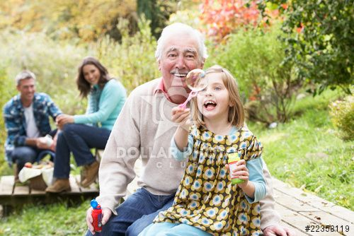 Grandfather And Granddaughter Blowing Bubbles On Family Picnic