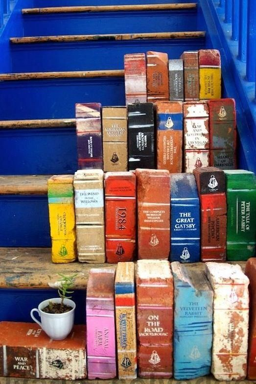 Bricks painted to look like books! Suzy you could do this and we could pit little piles of books near the benches in the garden. That would be so neat!