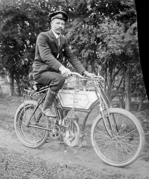 Alice Manfield, Man wearing a peaked cap and suit riding a motorised bicycle at Mount Buffalo, Victoria, Australia, ca. 1890s. Source: State...