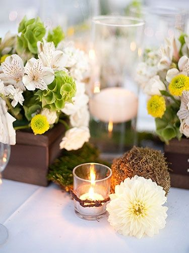 Stylistic Flowers And Candles Combination Used As Table Centerpiece