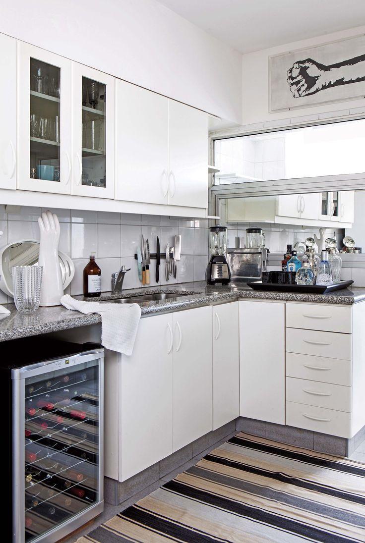 Cocina de un departamento con mesada de granito y alfombra a rayas. En la ventana que da al lavadero se reemplazó el vidrio por un espejo.
