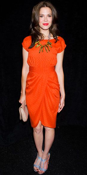 The orange of her dress, and that interesting necklace.