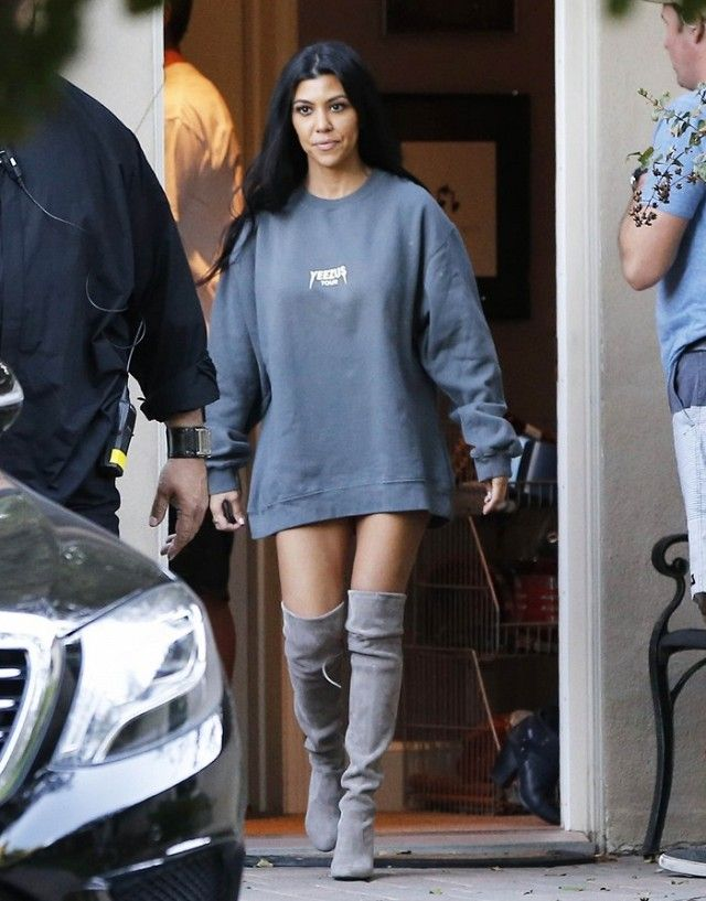 Kourtney Kardashian wears an oversized Yeezy sweatshirt with over-the-knee gray boots.