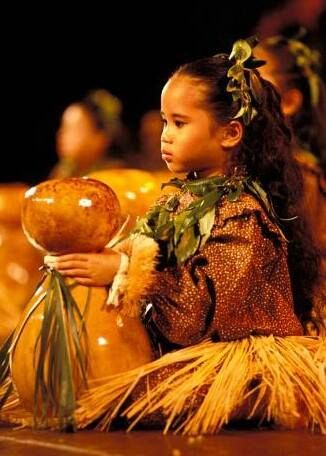 A young girl with an ipu heke, a Hawai'ian drum made from a hollow gourd. It is essential for traditional hula (hula kahiko).