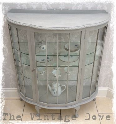 An amazingly beautiful display cabinet. The cabinet has been hand painted in Annie Sloan Paris Grey pain and waxed for protection.    The interior back has Laura Ashley Josette wallpaper in grey. There are 3 shelves to display items.    The cabinet does not have any distressed detail, this can however be done to customer requirements.        Dimensions: Width 100cm Depth 38cm Height 120cm    £195