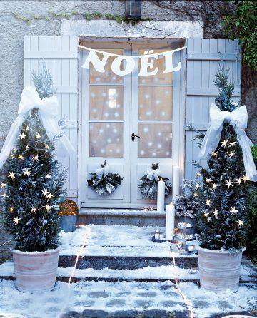 Une guirlande de Noël en carton plume blanc accrochée au dessus de la porte d'entrée