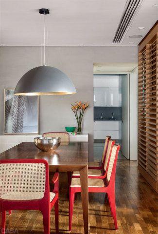 Uma textura cimentícia acinzentada (Argario) reveste as paredes da área social. Na sala de jantar, cadeiras do Arquivo Contemporâneo e foto de Thales Leite (HAP Galeria). A planta mostra a localização das venezianas.