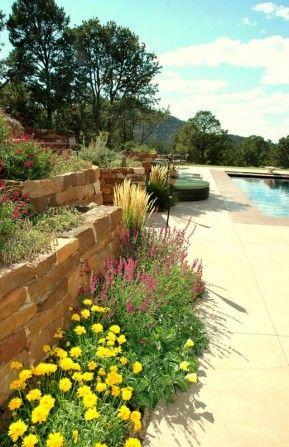 stone steps,tiki torch, terrace, terraced walls, poolside garden, pool, tumbling flowers, southwestern style garden, stone work, natural stone, rock work, stone walls, masonry walls