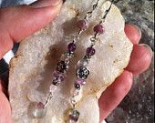 $38.50 USD    Only 1 available       .    Overview •Handmade item •Materials: Made with intention, Reiki infused, Gemstone healing, Amethyst, Rose Quartz, Fluorite, Lepidolite, Pink Tourmaline, Sterling Silver hooks, Fine Silver plated wire, glass seed beads, metal spacer beads, FREE SHIPPING REIKI Calming Amethyst Rose Quartz Lepidolite Pink Tourmaline Fluorite Wire Wrapped Earrings Blessed Gemstone Healing Sterling Silver Hooks