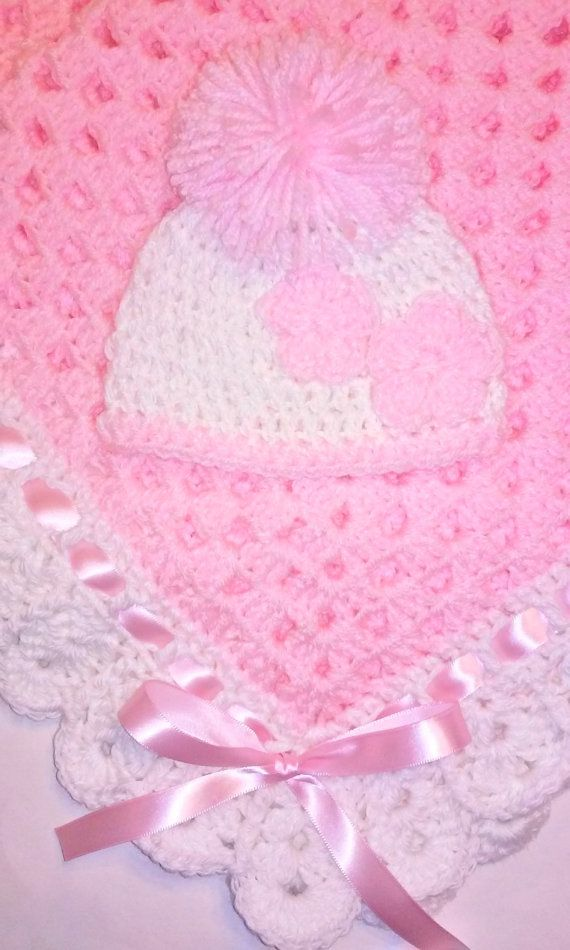 Very soft and cuddly pink granny square blanket with white crocheted scallop edging and pink satin ribbon. Matching newborn crocheted baby beanie hat in white with small pink flowers and pompom.  Made from 100% acrylic baby yarn for easy machine wash and dry. Perfect size for a stroller or car seat blanket.  Perfect baby shower gift. Blanket measures 34 inches x 34 inches Newborn Beanie: 12.5-13.5  Ready to ship today
