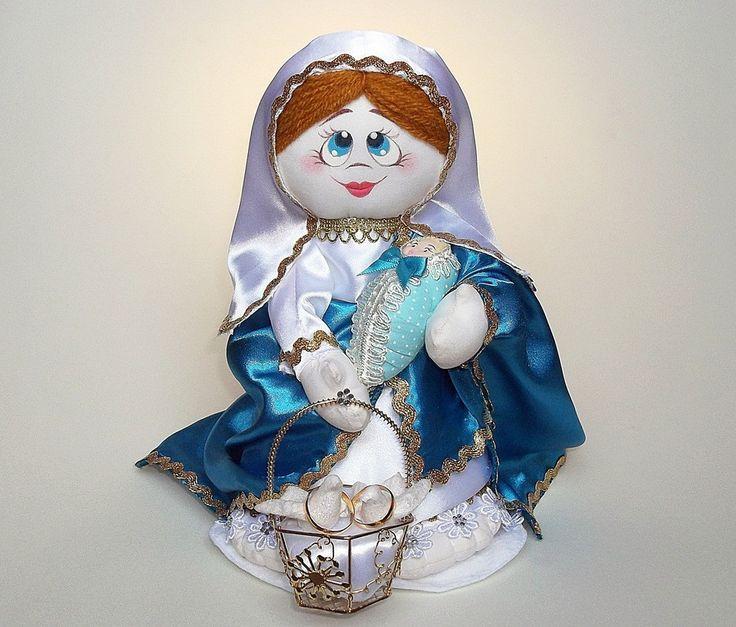 O SEU MOMENTO ESPECIAL COM DEVOÇÃO E FÉ! <br>A Nossa Querida Mãe Santíssima, também conhecida como Nossa Senhora do Conforto. <br> <br>DESCRIÇÃO: <br>- Boneca confeccionada com tecidos mistos. <br>- Decorada com aviamentos e adereços. <br>- Numa de suas mãos, há uma cestinha de metal decorada com dois pombinhos. Para melhor segurança, acrescentamos fitas para amarrar as alianças. <br>- Medidas aproximadas: 28cm de altura e 18cm de largura. <br>- Seu peso aproximado: 390g. <br> <br>DÚVIDAS E…