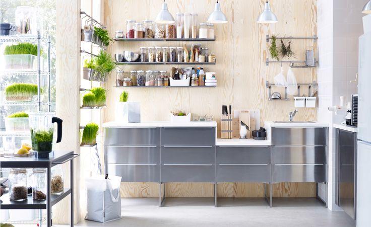 Keuken met roestvrijstalen IKEA elementen, wand met houtpanelen, witte accessoires en veel groen