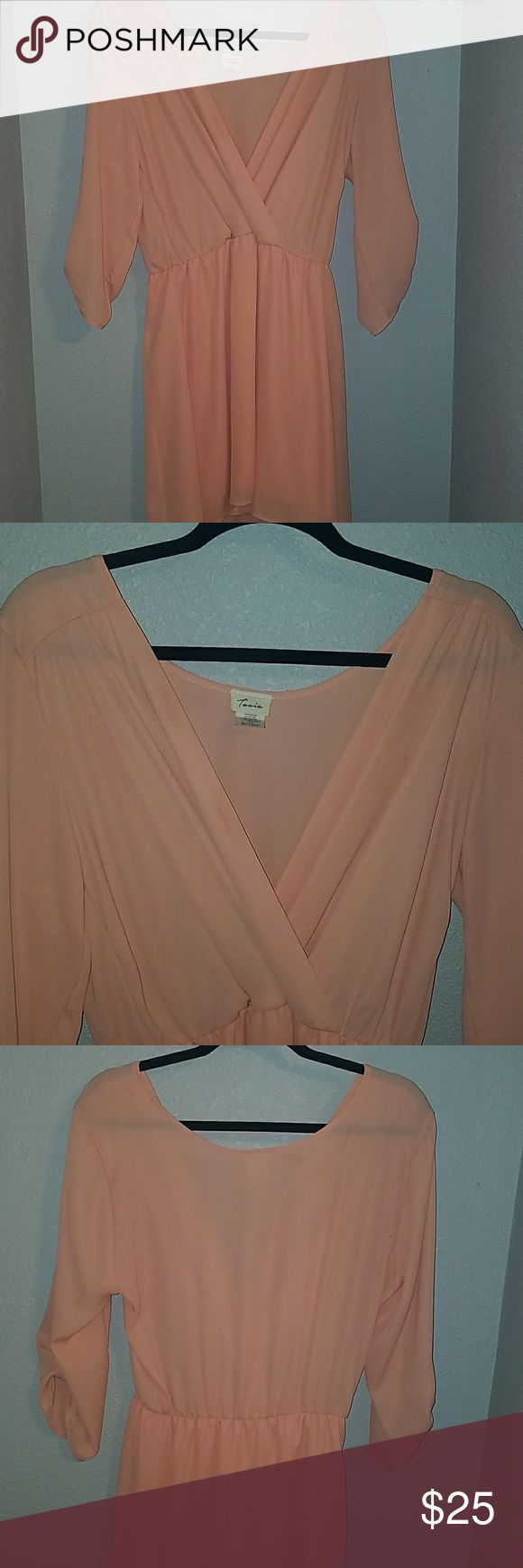 Beautiful Salmon colored dress! Beautiful deep v-neck dress it's a light pink / salmon color three-quarter length sleeve. It is a little above knee length. I took the tags off thinking I was going to wear it but it was too short for me and I never wore it. tovia Dresses Midi