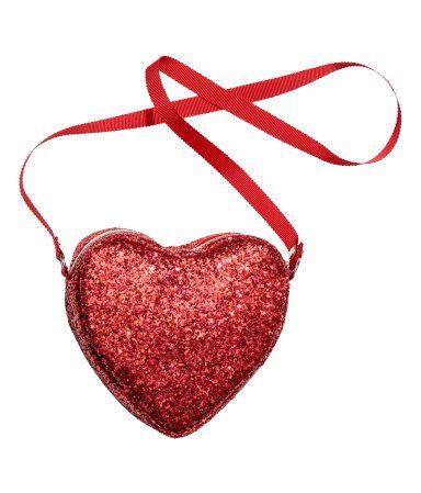 Röd. En hjärtformad axelremsväska i läderimitation med glittrig yta. Väskan har dragkedja upptill samt axelrem av ripsband. Fodrad. Storlek ca 13x14 cm.