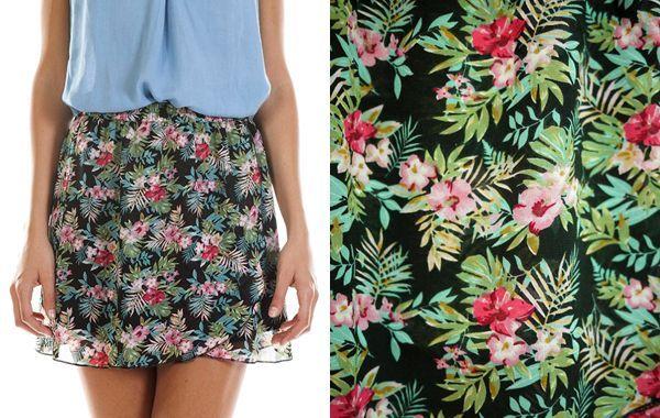 Falda corta cruzada con cinturilla elástica. Está confeccionada con tejido de gasa con estampado de flores multicolor sobre fondo negro. Prenda forrada.