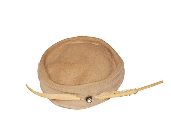 ITEM DETAILS Approx. Hat Size: Hat Size: 20 (51 cm); Outside Diameter: 9 (23 cm); Height of Crown 2 (5 cm) Condition: Hat is good shape overall. One small hole on the top, see final photo Mark/Label: Glenover felt One of a kind vintage item – Buy Now Very snazzy tan pill box with gathered tan crinoline netting around the sides. Decorated with a large center rhinestone and long lacquered quill feather for maximum impact. Inset crown. #Hat260 If you arent already a Madge VIP get $20 off...