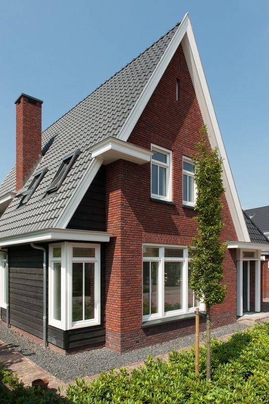 Steile daken met keramische dakpannen, combinatie van rode handvorm bakstenen met houten afwerking