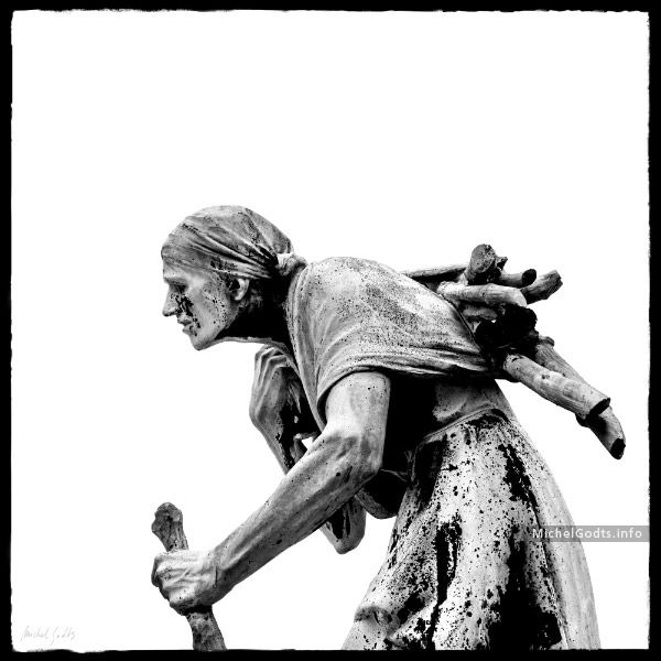 Contemporary photographic rendition of a late 19th century bronze statue representing an old woman carrying wood logs on her back—an allegory for winter. Signed or unsigned photography print for art collectors or for a wall decor.