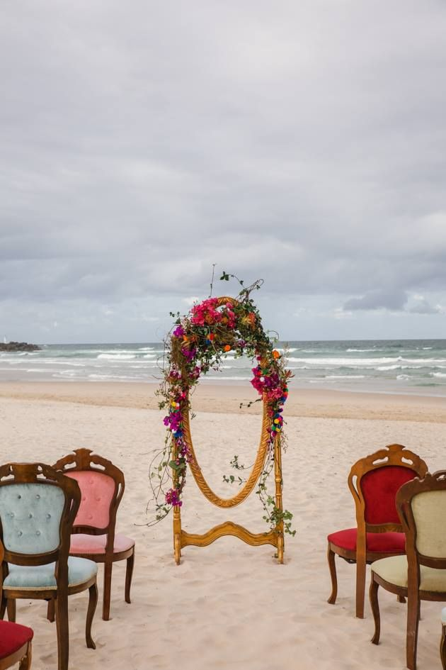 Flowered timber frame complemented by vintage chairs on the beach add a hint of luxe.
