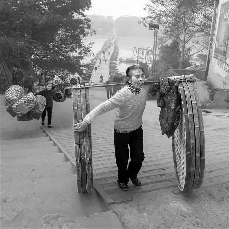 一个农妇挑着她编织好的竹簸箕,到市场去卖。这是她在赶往集市的路上,路过一座浮桥,登上河堤后,看到即将到达集市时,露出的喜悦表情。