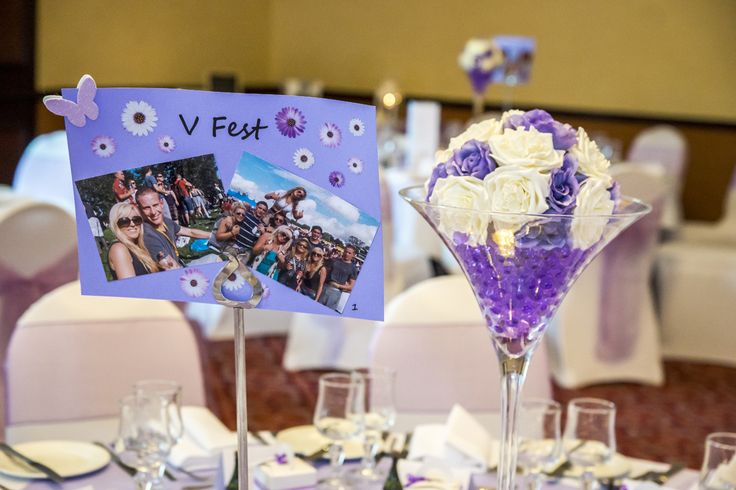Lovely lilac and white flower setup for a centrepiece, and the name of the table with some pictures of the wedded couple from that place.