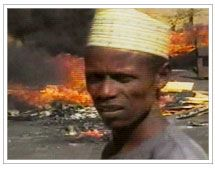 Nigerian man in the foreground of a fire.. video 17 mins